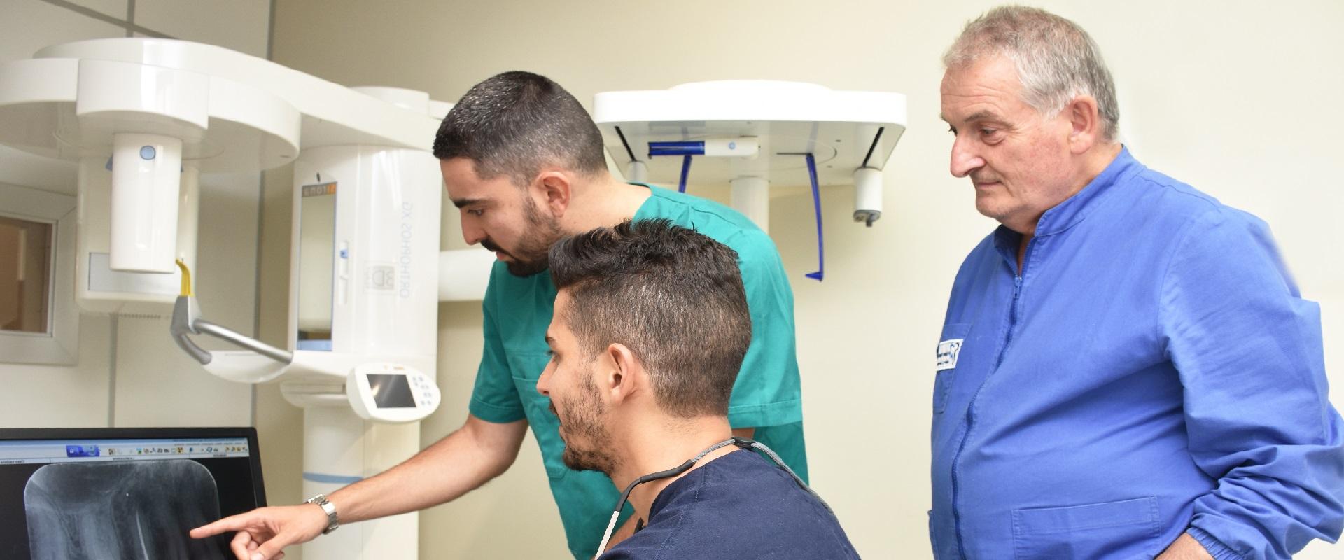 Staff medici visiona lastra per otturazione carie